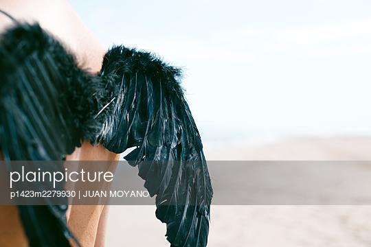Man wearing black feather wings outdoors - p1423m2279930 by JUAN MOYANO