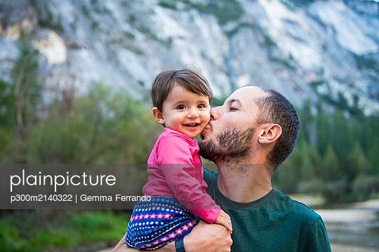 Portrait of happy baby girl kissed by her father, Yosemite National Park, California, USA - p300m2140322 by Gemma Ferrando