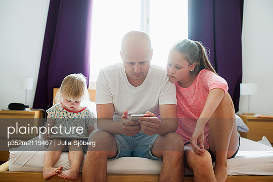 Father with his daughters using technology - p352m2119407 by Julia Sjöberg