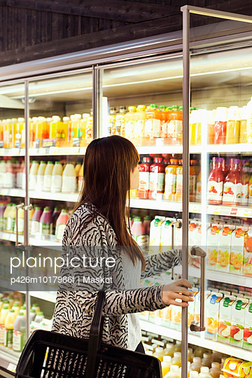 Woman shopping at freezer section in supermarket - p426m1017986f by Maskot