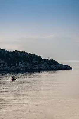 A lone boat is heading out to sea in the golden morning light - p1433m1585624 by Wolf Kettler
