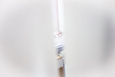 Baby asleep in the crack of a door - p1513m2221801 by ESTELLE FENECH