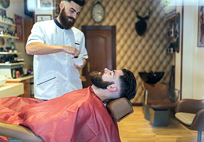 Barber preparing shave for a customer - p300m1081606f by Marco Govel