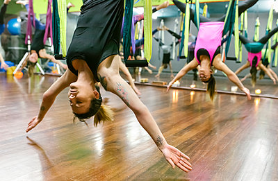 Group of women having a class of aerial yoga - p300m1416862 by Marco Govel