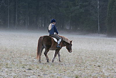 A girl with long blond hair on a frozen field, Sweden - p348m733638 by Bertil Hertzberg