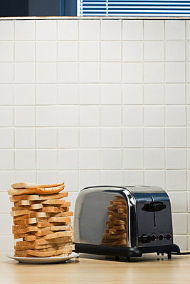 Stack of toast and toaster - p9243119f by Image Source