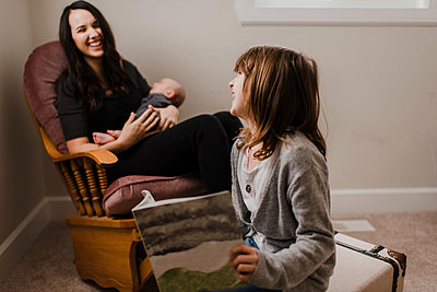 Girl laughing with mother while she cradles baby brother in living room armchair - p924m2136930 by Kymberlie Dozois Photography