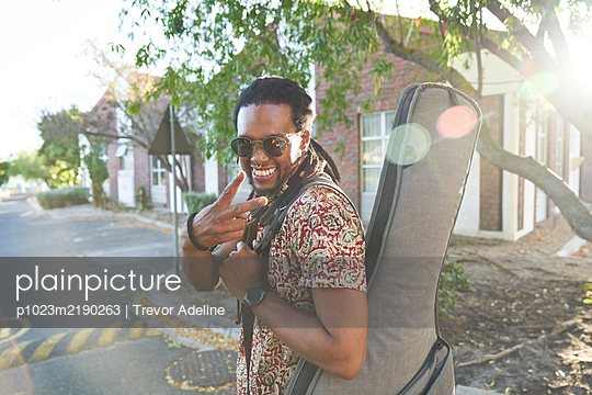 Portrait happy male musician with guitar case gesturing peace sign - p1023m2190263 by Trevor Adeline