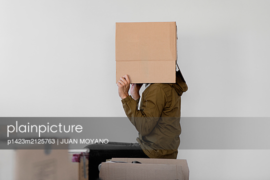 Man with a brown cardboard box in his head - p1423m2125763 by JUAN MOYANO