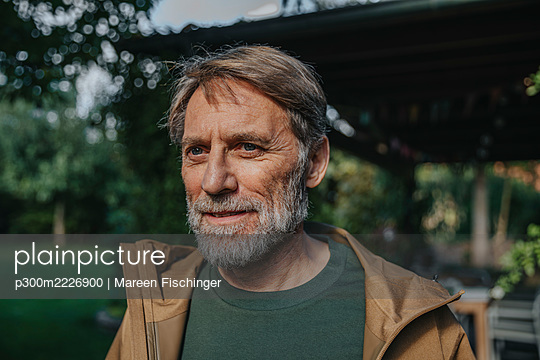 Mature man looking away while standing in back yard - p300m2226900 by Mareen Fischinger