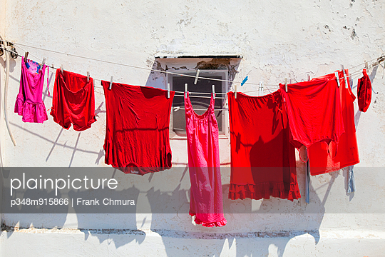 Red washed clothes drying in sunlight, Procida, Naples, Italy - p348m915866 by Frank Chmura