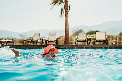 Side angle view of little girl in pink hat swimming in pool - p1166m2218207 by Cavan Images