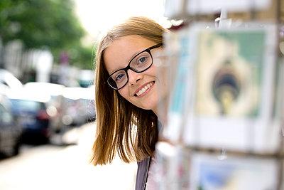 Jugendliche lugt hinter dem Postkartenständer hervor - p1212m1178986 von harry + lidy