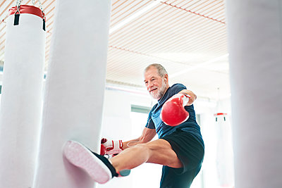 Fit senior man in boxing gloves fighting - p300m1449866 by HalfPoint