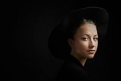 Portrait of young woman against black background - p300m1568354 von Philipp Dimitri