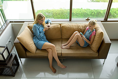 Mother and daughter sitting in modern living room on a couch using smartphones - p300m1587669 von Steve Brookland