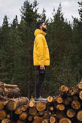 Man with camera standing on stack of wood - p300m2060843 by Kike Arnaiz