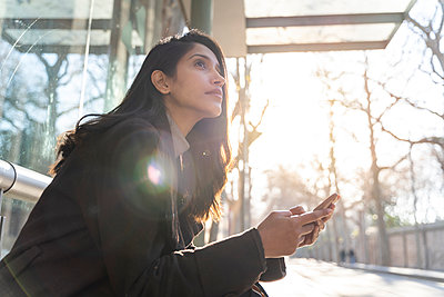 Young woman with smartphone waiting at the tram stop - p300m2166177 by VITTA GALLERY