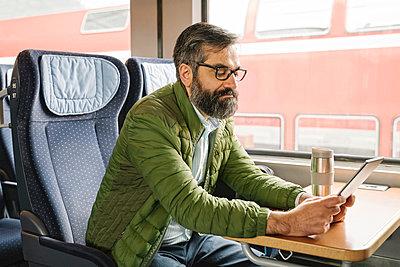 Man sitting in train using tablet - p300m2188150 by Hernandez and Sorokina
