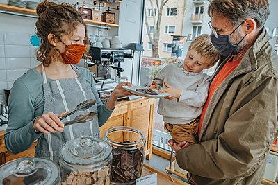Little boy being served chocolate in candy shop, Cologne, NRW, Germany - p300m2256166 von Mareen Fischinger