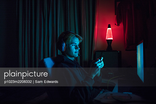 Teenage boy in headset playing video game in dark bedroom - p1023m2208332 by Sam Edwards