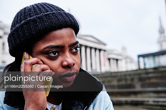 Outdoor portrait of a Young black African American young woman speaking on mobile phone - p1166m2255350 by Cavan Images