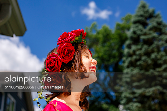 A beautiful girl with a crown of roses smiles under a blue sky - p1166m2268856 by Cavan Images