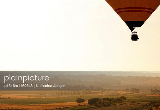 Ein Heissluftballon während einer Ballonfahrt über der sonnendurchfluteten Landschaft von Mallorca, nahe Manacor, Mallorca, Balearen, Spanien, Europa - p1316m1160943 von Katharina Jaeger