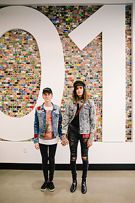Young couple in denim jackets holding hands by large numeric sign - p1192m2110306 by Hero Images