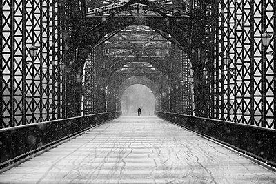 Einsamer Fußgänger auf einer Brücke - p1696m2294406 von Alexander Schönberg