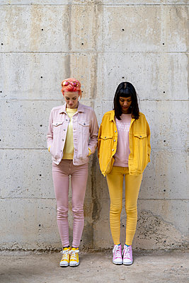 Two alternative friends having fun, wearing yellow and pink jeans clothes, looking down - p300m2023645 by VITTA GALLERY