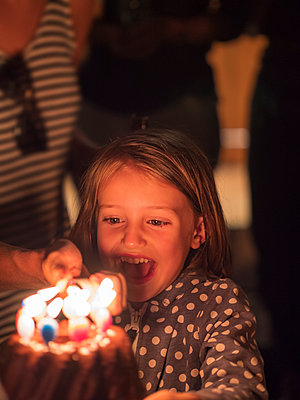 Little girl looking at burning candles on a birthday cake - p300m2140876 by Albrecht Weißer