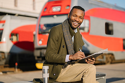 Portrait of happy businessman with reusable cup and documents waiting for the train - p300m2155322 by Hernandez and Sorokina