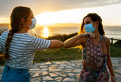 Women in protective face masks elbow bumping against sky during COVID-19 outbreak - p300m2221422 by Marco Govel