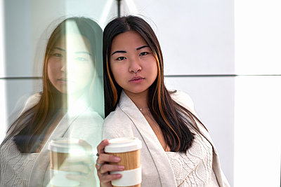 Young woman with coffee cup leaning against glass wall - p300m2256721 by Veam