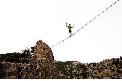 A male highliner walks the Elephant Buttresses highline in Boulder Canyon - p343m801176f by Kyle Sparks
