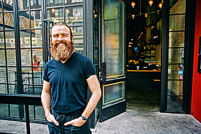 Caucasian man with beard smiling on sidewalk - p555m1305268 by Peathegee Inc