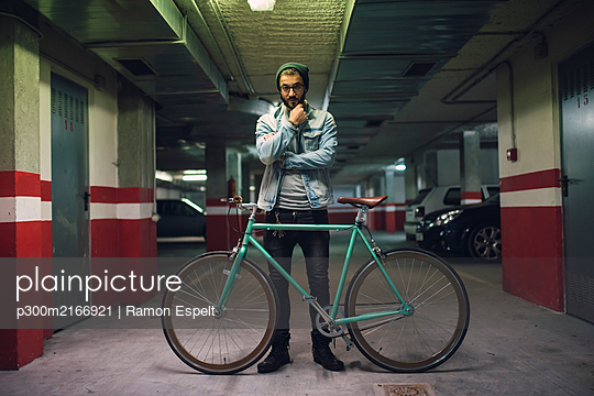 Young man standing in park house with his fixie bike - p300m2166921 by Ramon Espelt