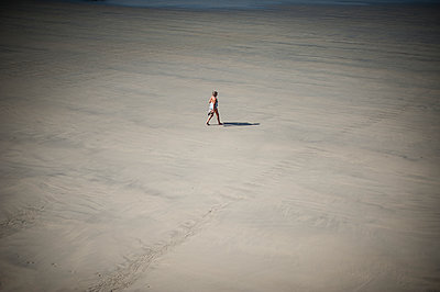 Single woman walking on beach - p1007m1216535 by Tilby Vattard