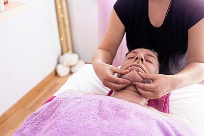 Female masseuse massaging a male patient's face - p1166m2194078 by Cavan Images