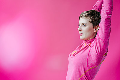 Woman in pink sportswear stretching her arms - p300m1535251 by Kniel Synnatzschke