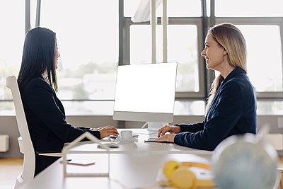 Two businesswomen sitting at desk in office talking - p300m2156289 by Joseffson