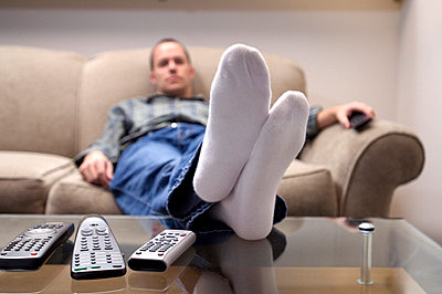 Man sitting on couch, watching television - p3720383 by James Godman