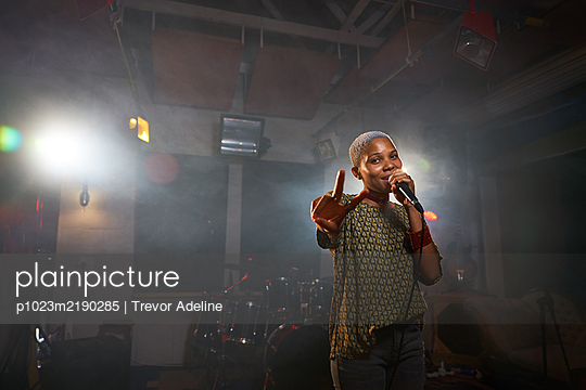 Portrait cool female musician singing and gesturing peace sign - p1023m2190285 by Trevor Adeline