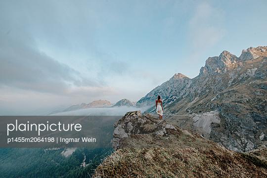 Woman enjoys a beautiful sunrise up at Mangart Mountain in Slovenia - p1455m2064198 von Ingmar Wein