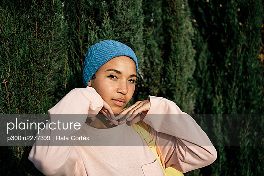 Beautiful woman in knit hat standing in front of lush foliage - p300m2277399 by Rafa Cortés