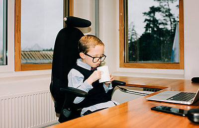 young boy drinking coffee in his dads office at work - p1166m2153348 by Cavan Images