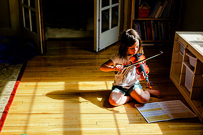 A small child sits alone in a patch of sunlit playing violin - p1166m2171952 by Cavan Images