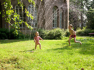 Children playing under the sprinkler - p1231m1059785 by Iris Loonen