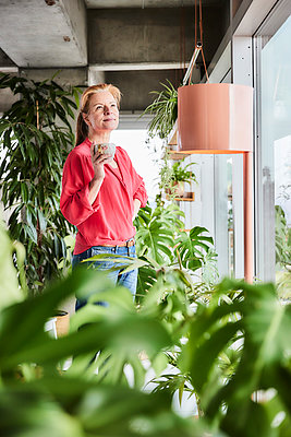 Thoughtful woman with coffee cup standing amidst plants at home - p300m2266086 by Jo Kirchherr